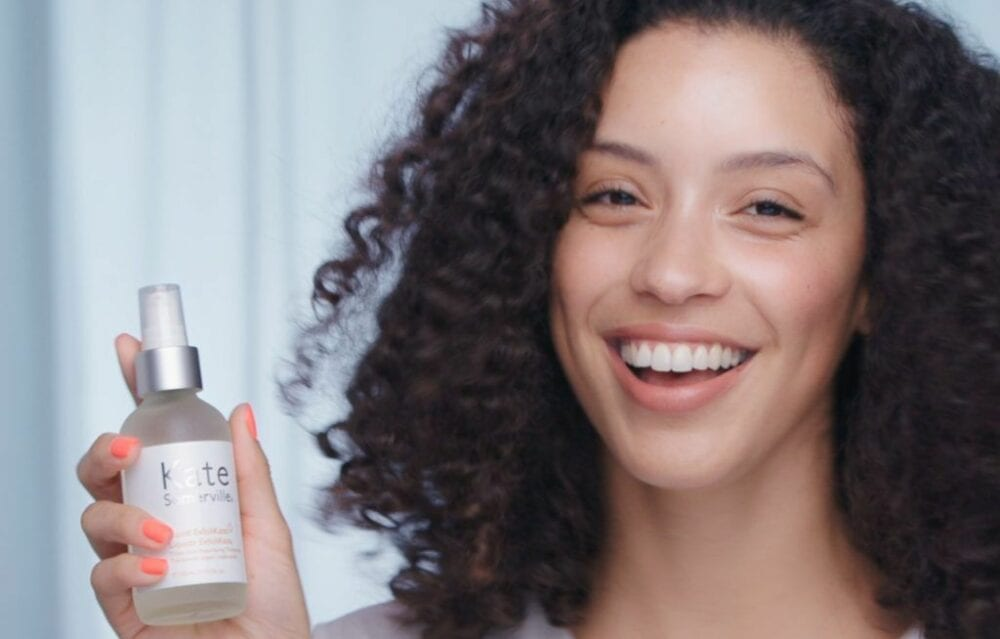 Woman holding Kate Somerville skincare product