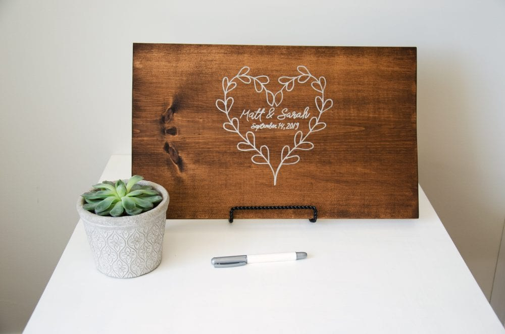 Wood slab guest book with decorative plant and marker