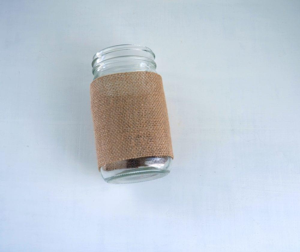 Mason jar with burlap wrapped around it