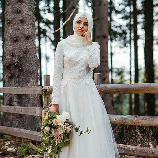 brides with long sleeves posing on bridge