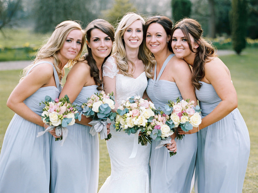 Bride with bridesmaids wearing pale blue dresses