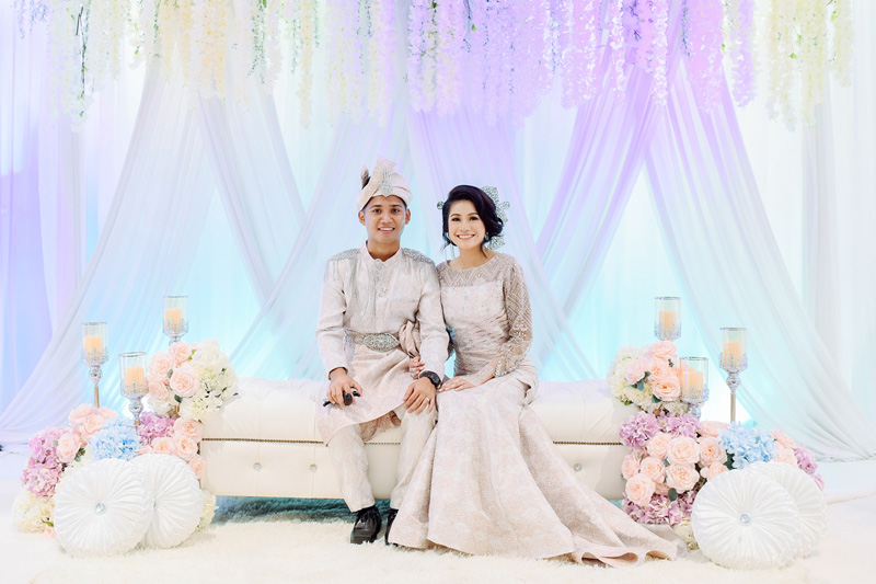 Bride and groom in front of pastel blue & lavender drapes