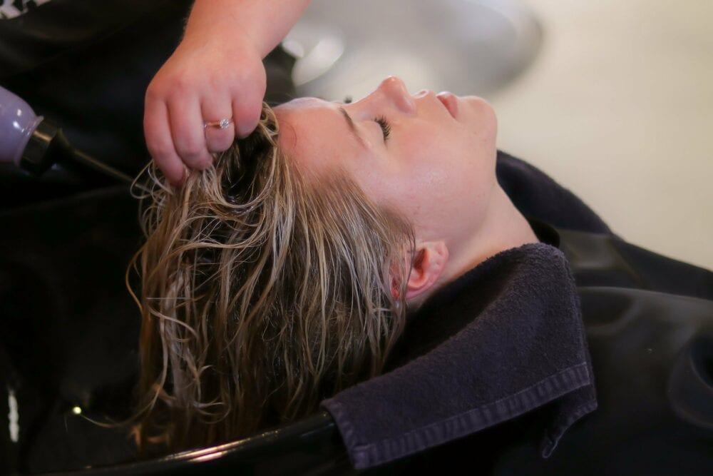 Woman having her hair washed by stylist