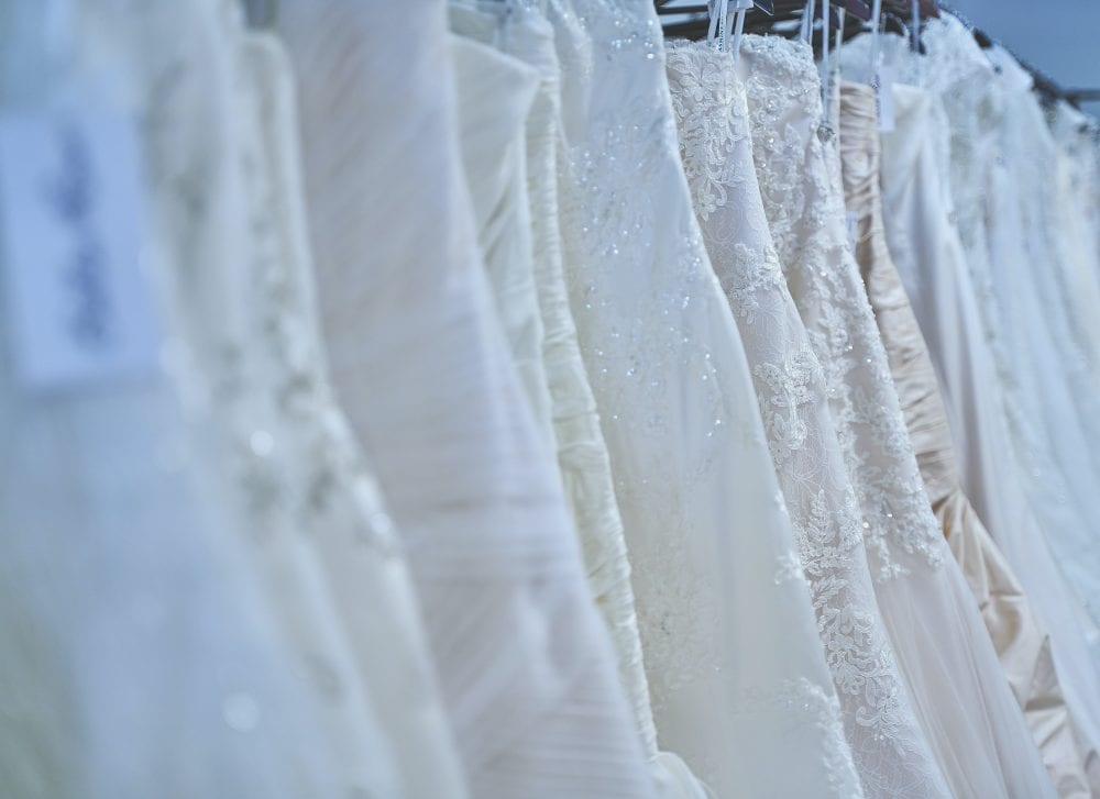 clothing rack full of wedding dresses
