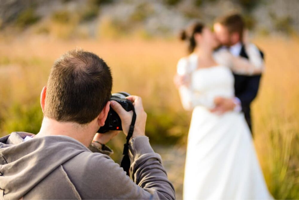 Photographer taking a photo of a bride & groom