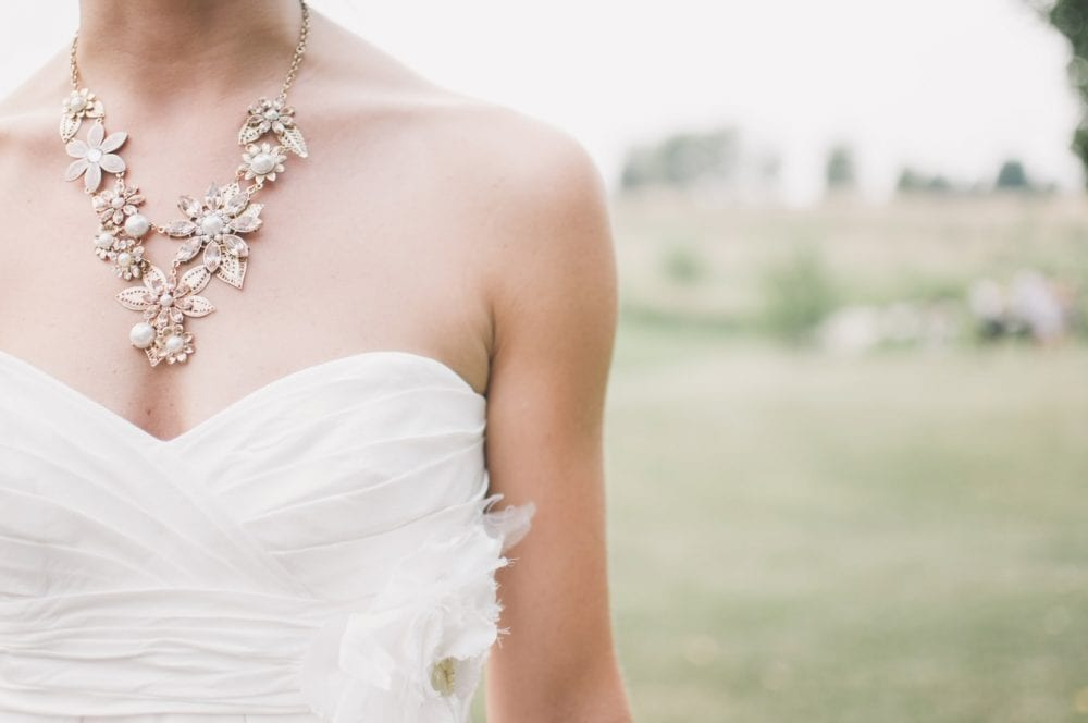 bride wearing sweetheart wedding dress with a big flower necklace