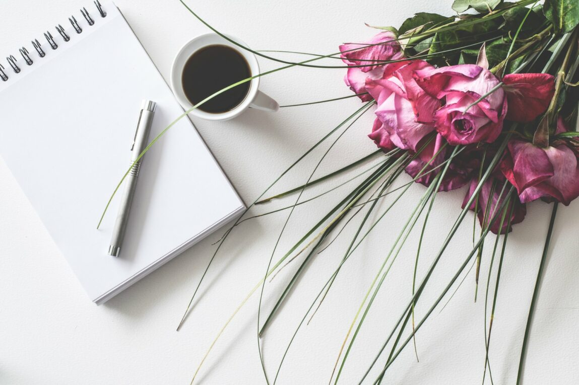 notepad and coffee with flower bouquet