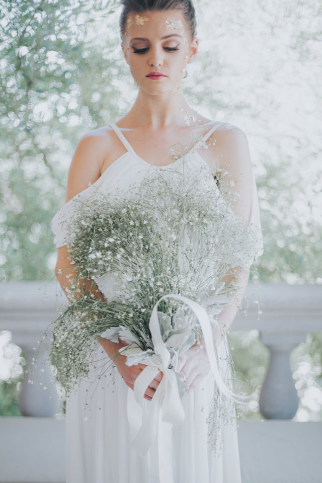 A golden Grecian bridal inspiration shoot styled with a modern braid, a simple baby's breath bouquet and small flakes of gold adorning the bride's face by Blue Rose Studio